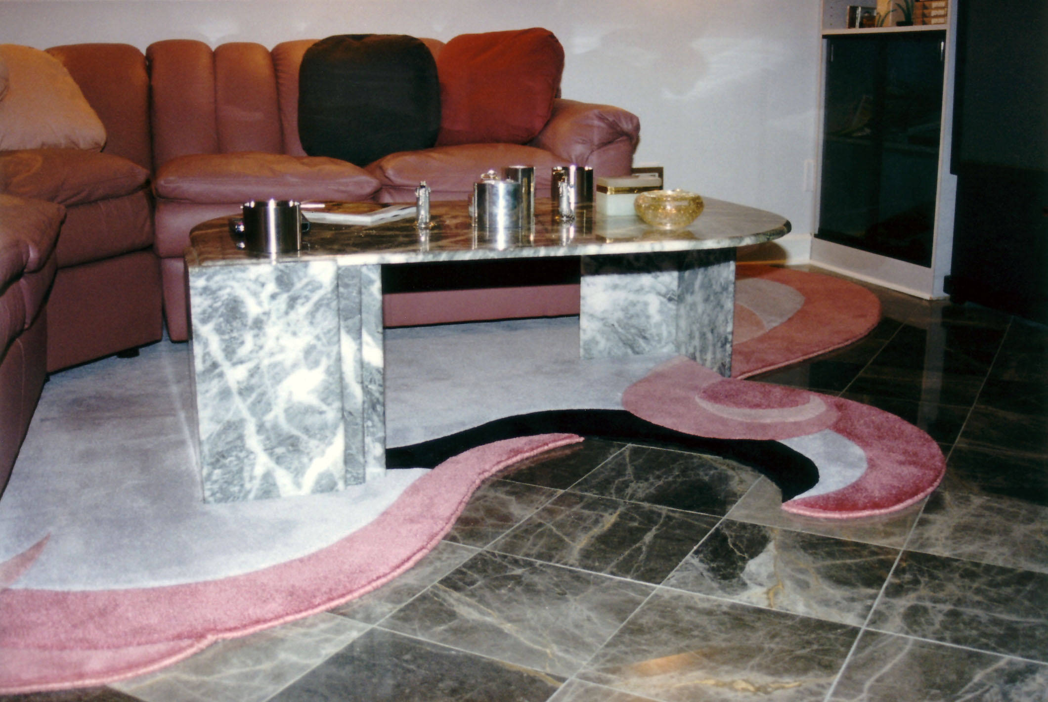 The lines, texture and colors of this custom rug, styled by David enhance both the leather sofa, and the marble floors.